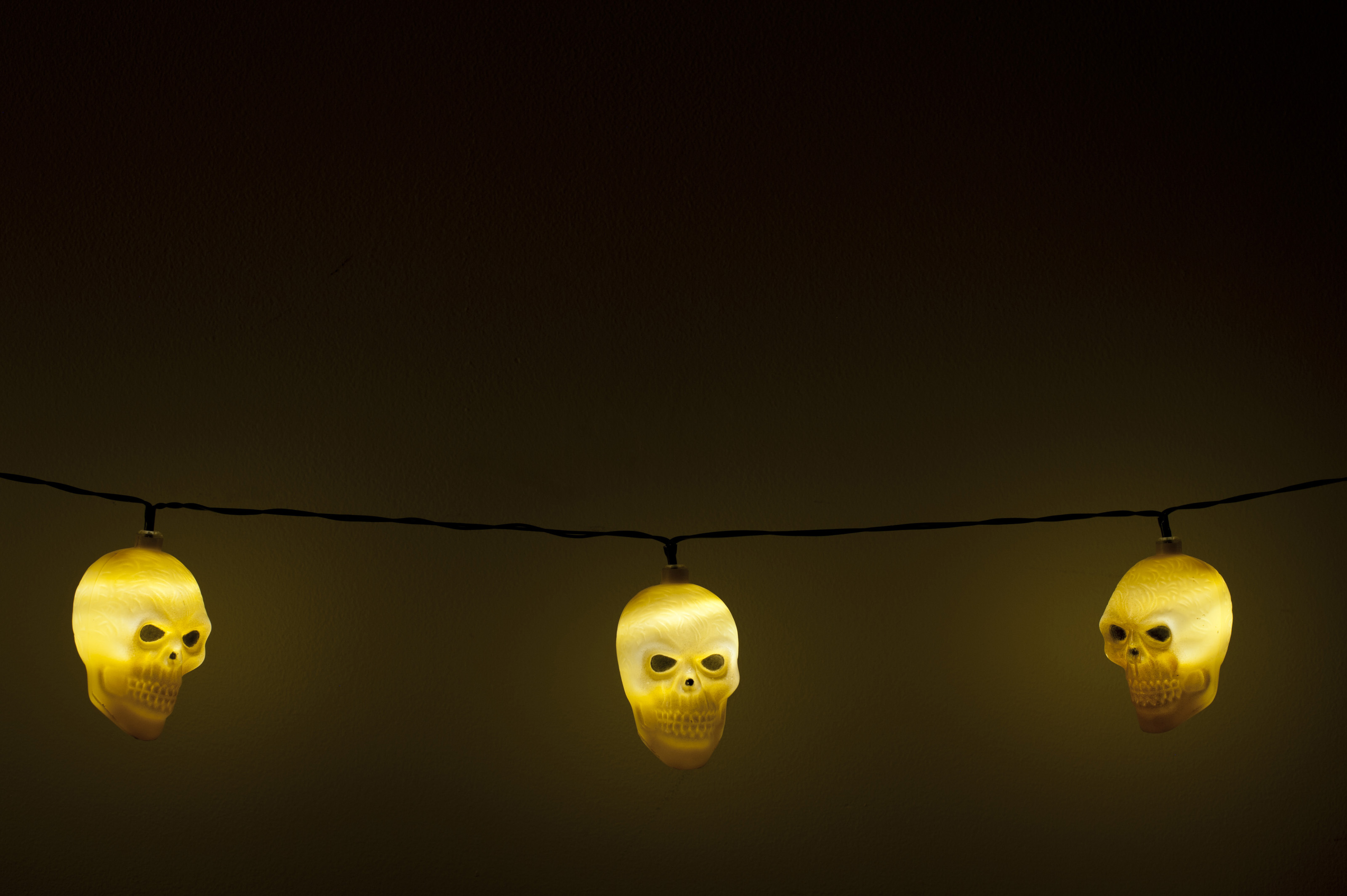 Three spooky glowing yellow Halloween skull lights forming a lower border in the darkness with copy space for your festive greeting