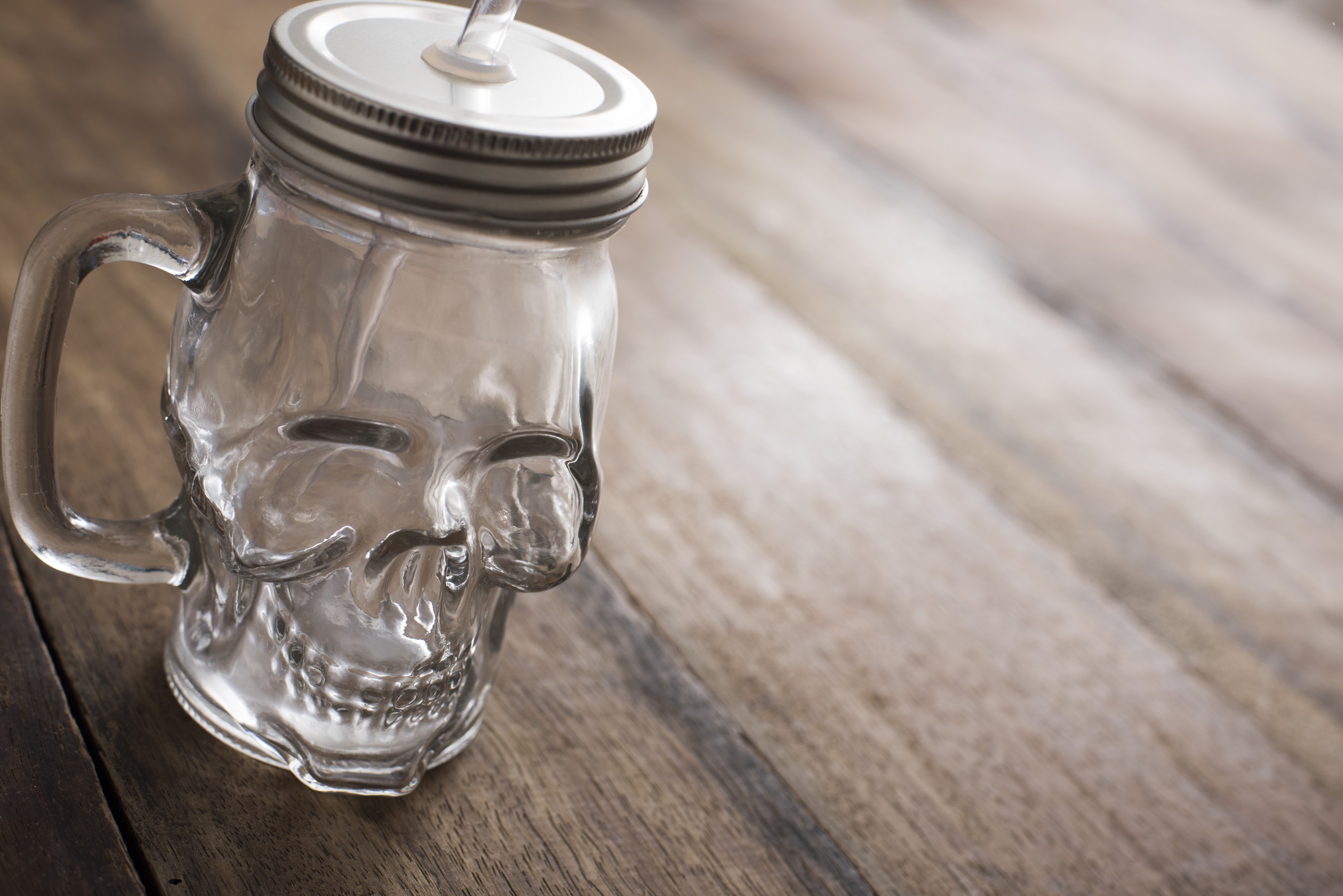 Novelty glass mason jar with lid shaped like scull having been placed on a wooden table