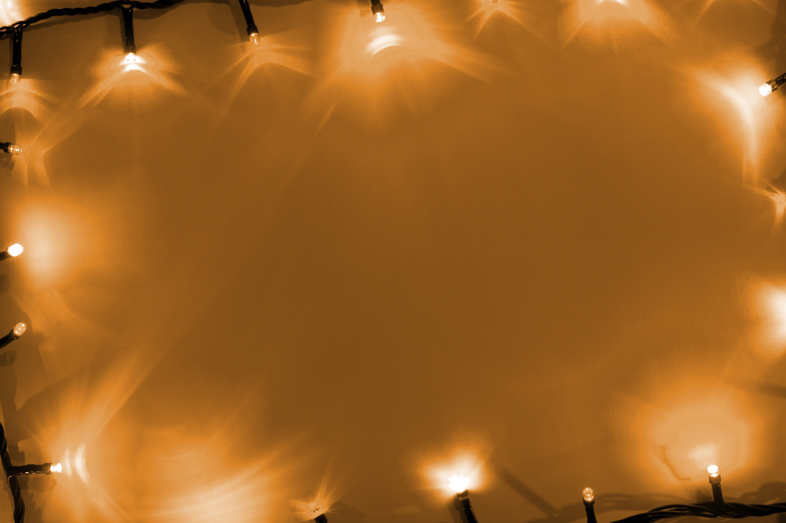Frame of shining Halloween lights pointing inwards on an orange background with copy space
