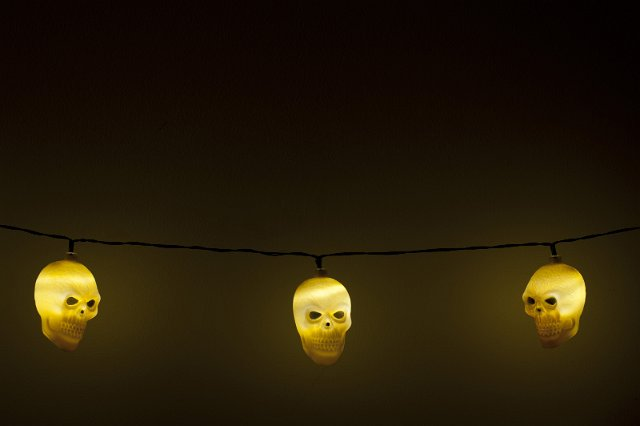 image of three glowing yellow halloween skull lights