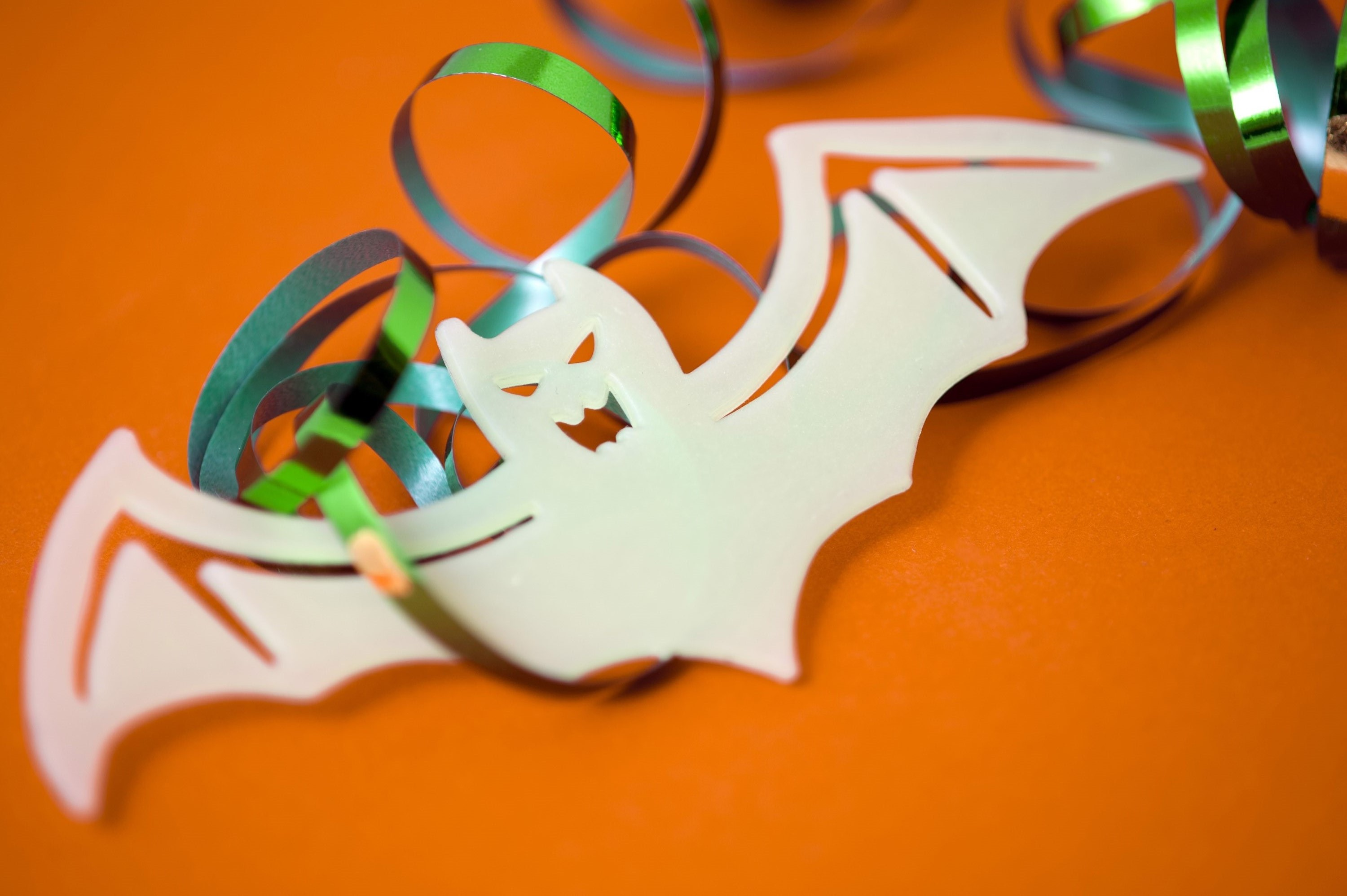 Halloween bat decoration with party streamers on a festive orange background