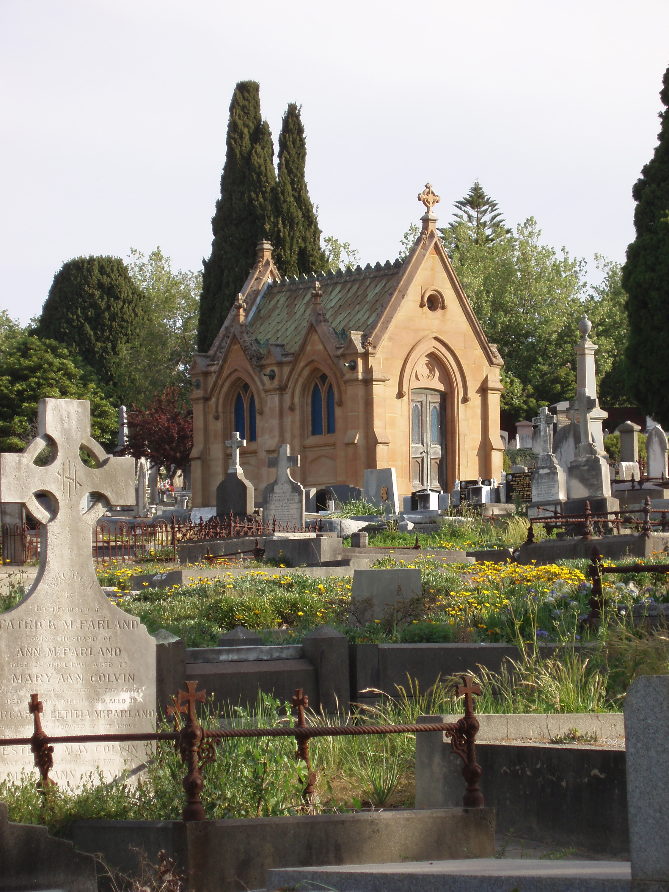 headstones and a small stone crypt in a cemetery