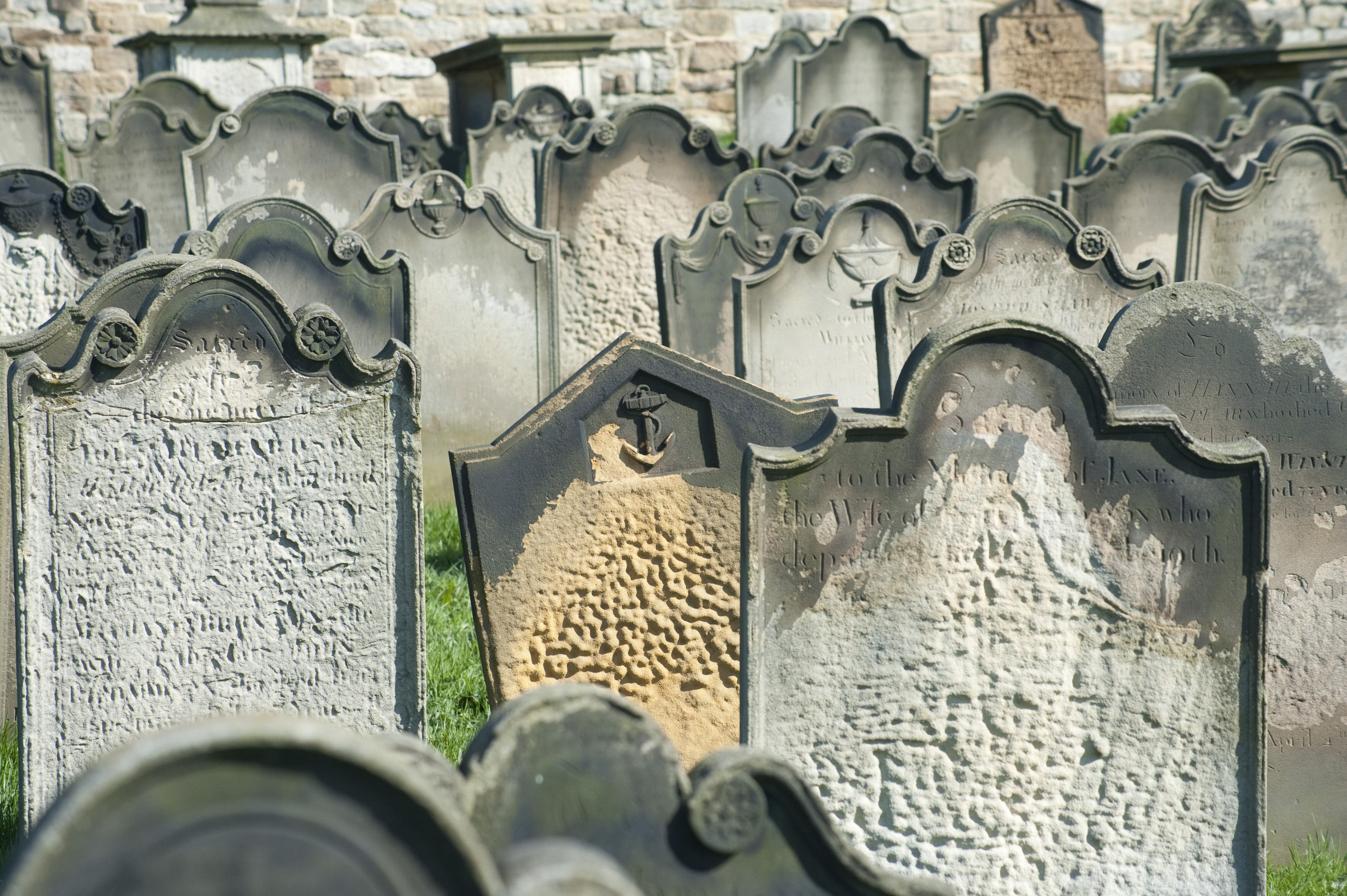 rows of old weathered headstones in a church cemetery