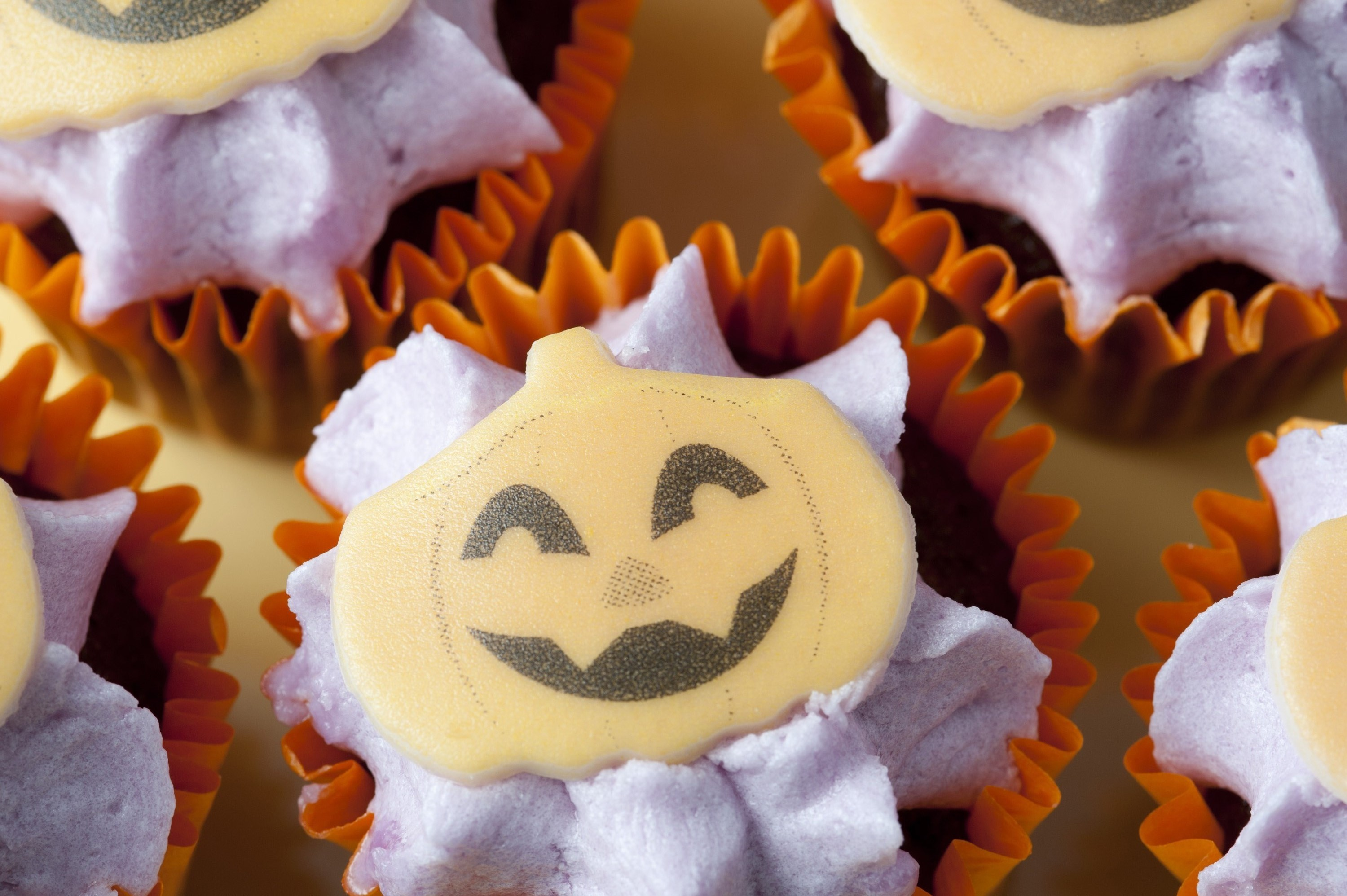 miniature halloween decorated party cup cakes with jack-o-lantern faces