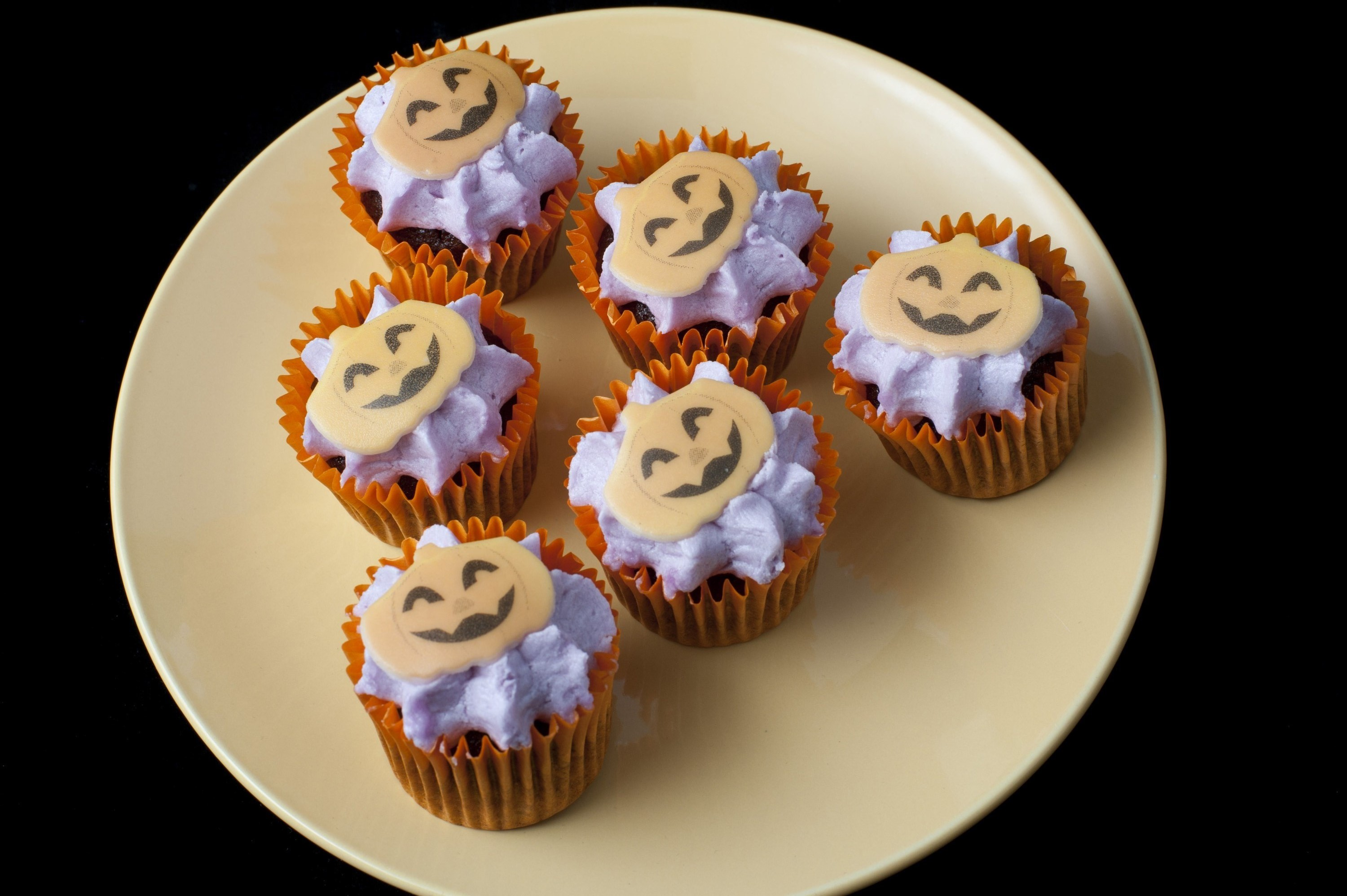 a plate with some halloween decorated iced mini cup cakes