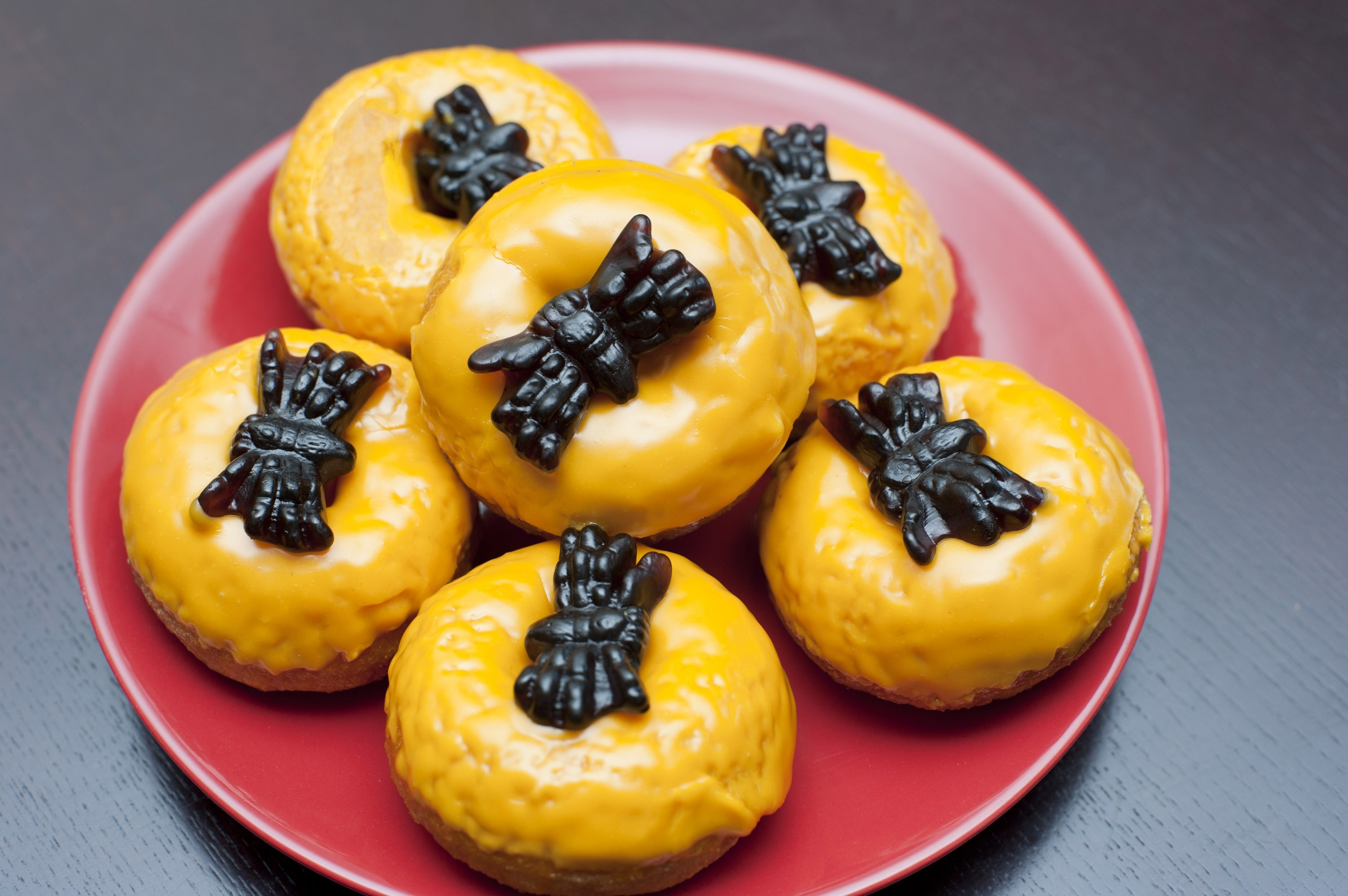 Orange glazed Halloween doughtnuts decorated with black jelly spiders for a fun Halloween party or to be handed to the kids for trick-and-treating