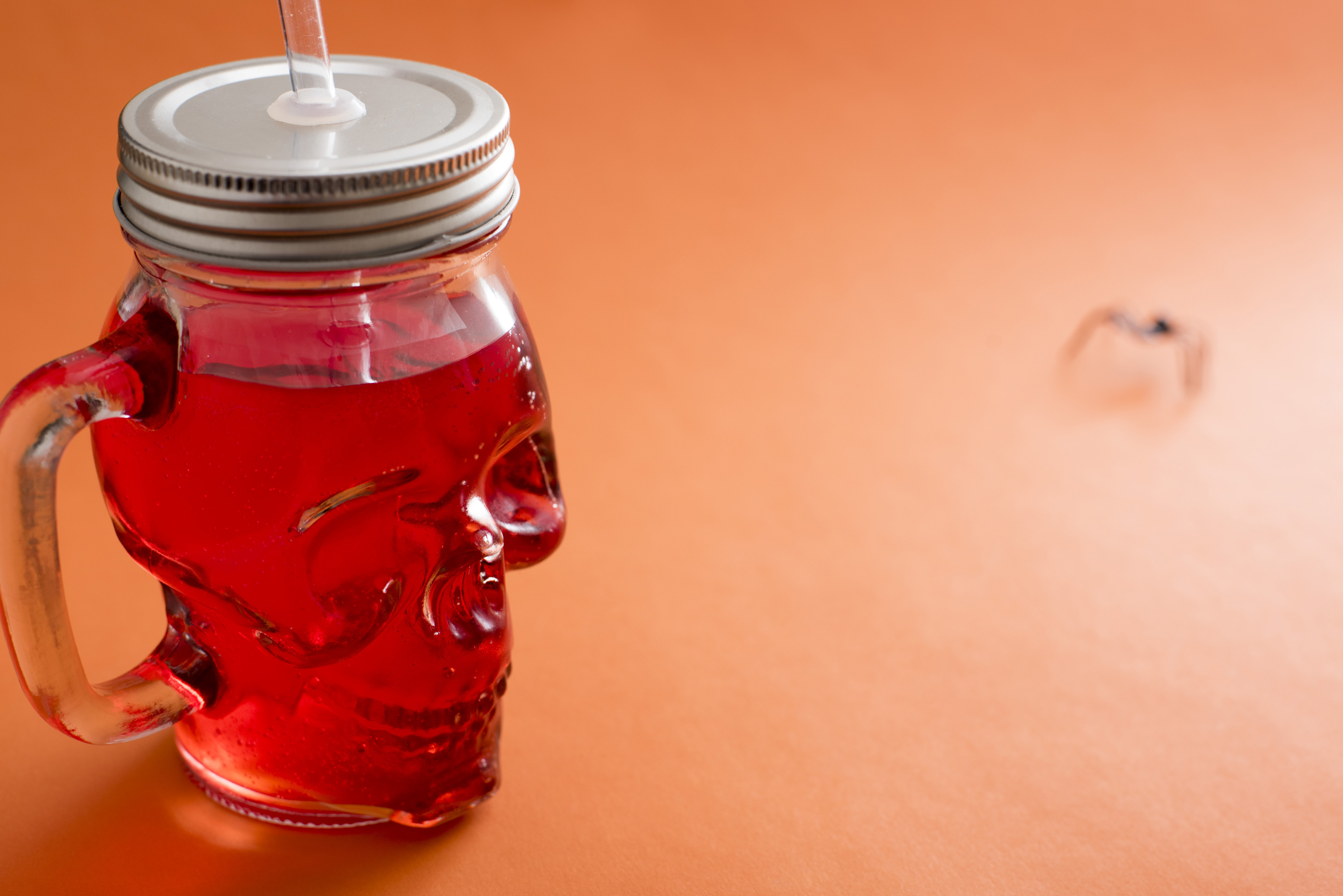 Red Halloween drink in a skull shaped glass mason jar with straw over a graduated red background with copy space