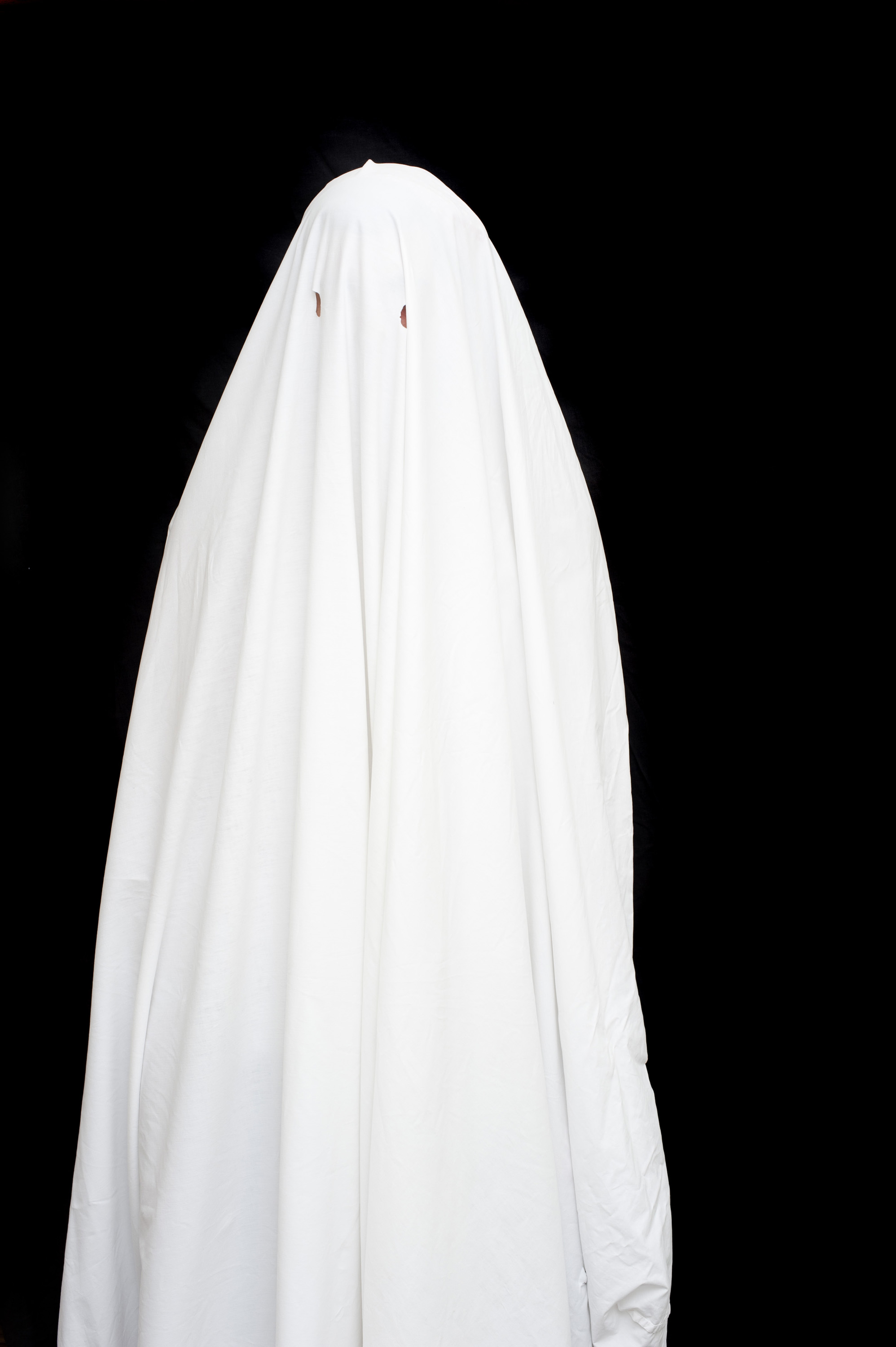 a bed sheet halloween ghost standing forlorn