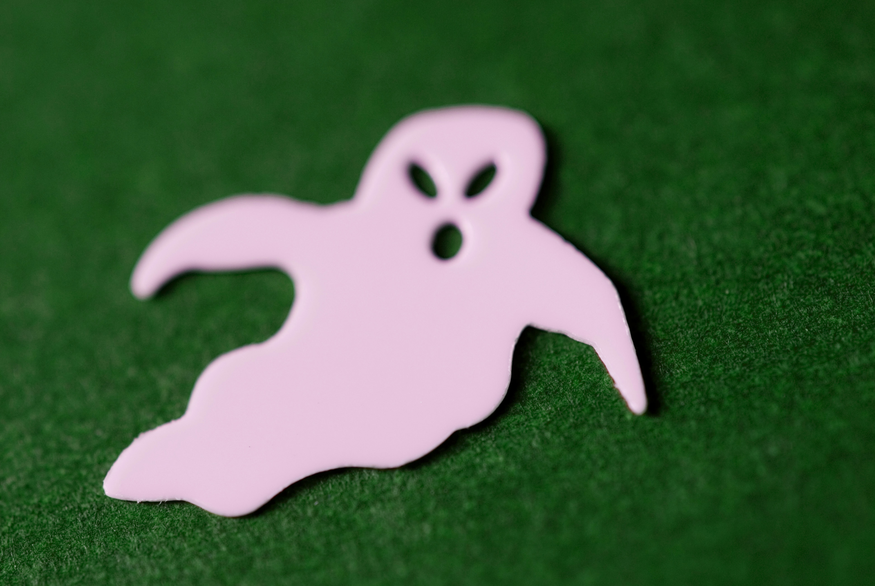 white ghost outline shape on green background