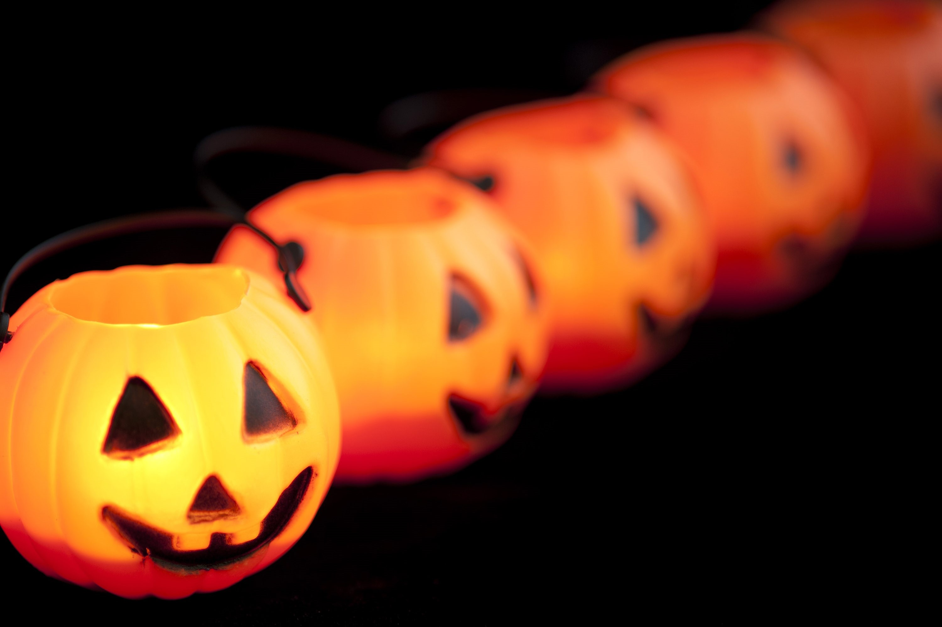 Row of creepy Halloween lantern ornaments arranged in a diagonal receding row with focus to the first lantern on the left, over a dark background