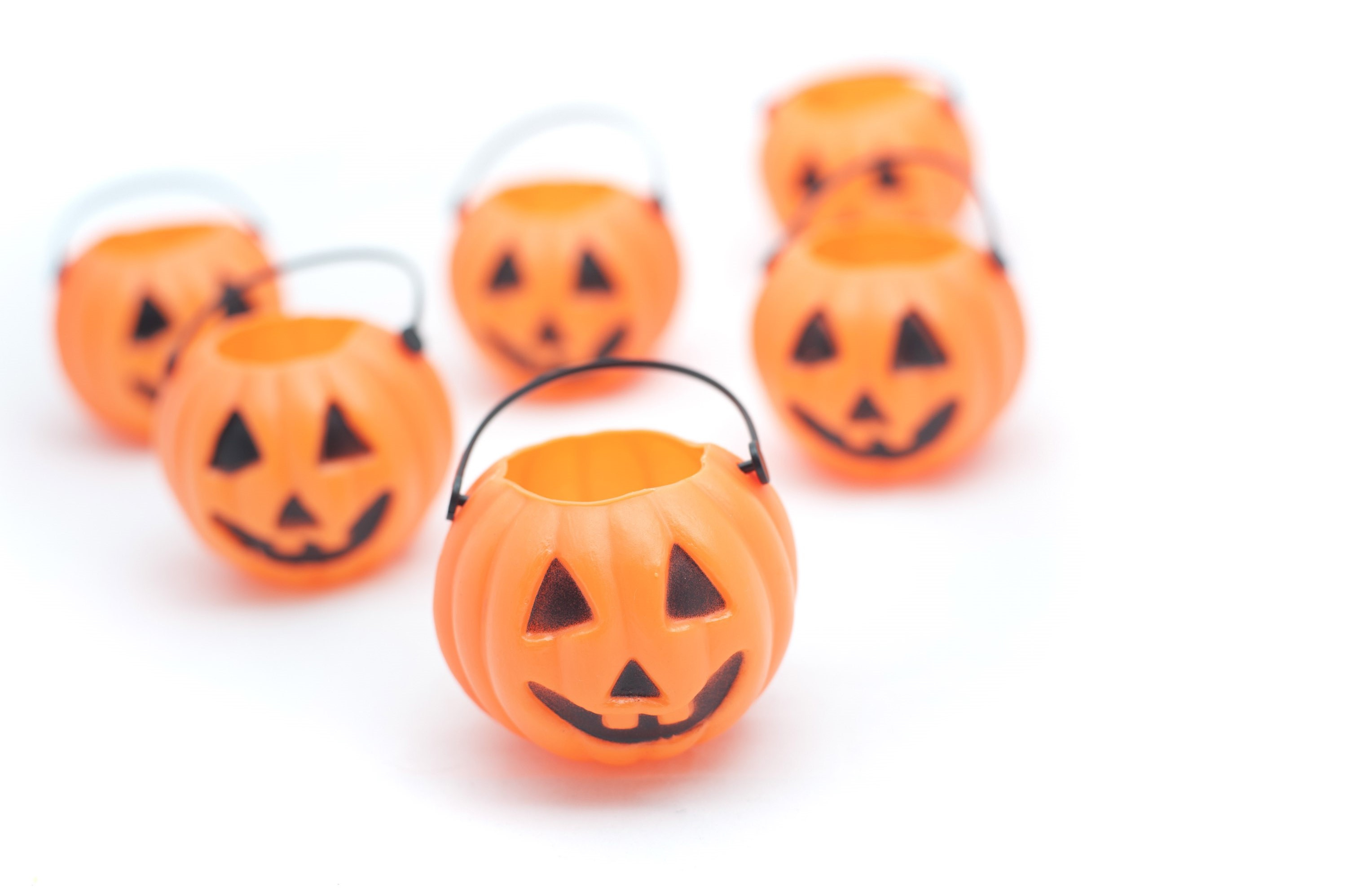 Group of Halloween decorations in the form of ceramic jack o lanterns or orange pumpkins wih scary faces over a white background