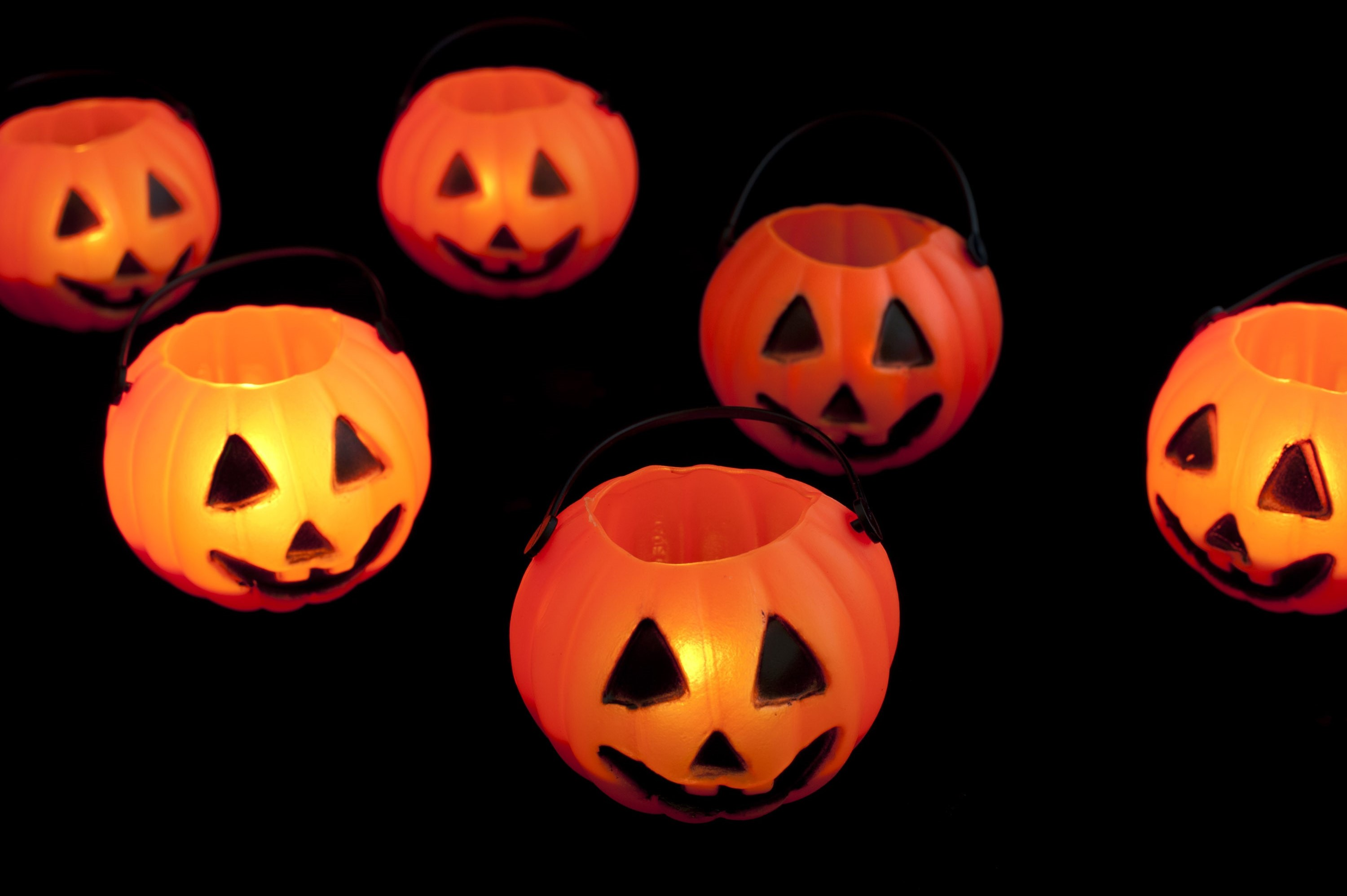 black background with orange glowing jack-o-lantern candle lights with spooky faces