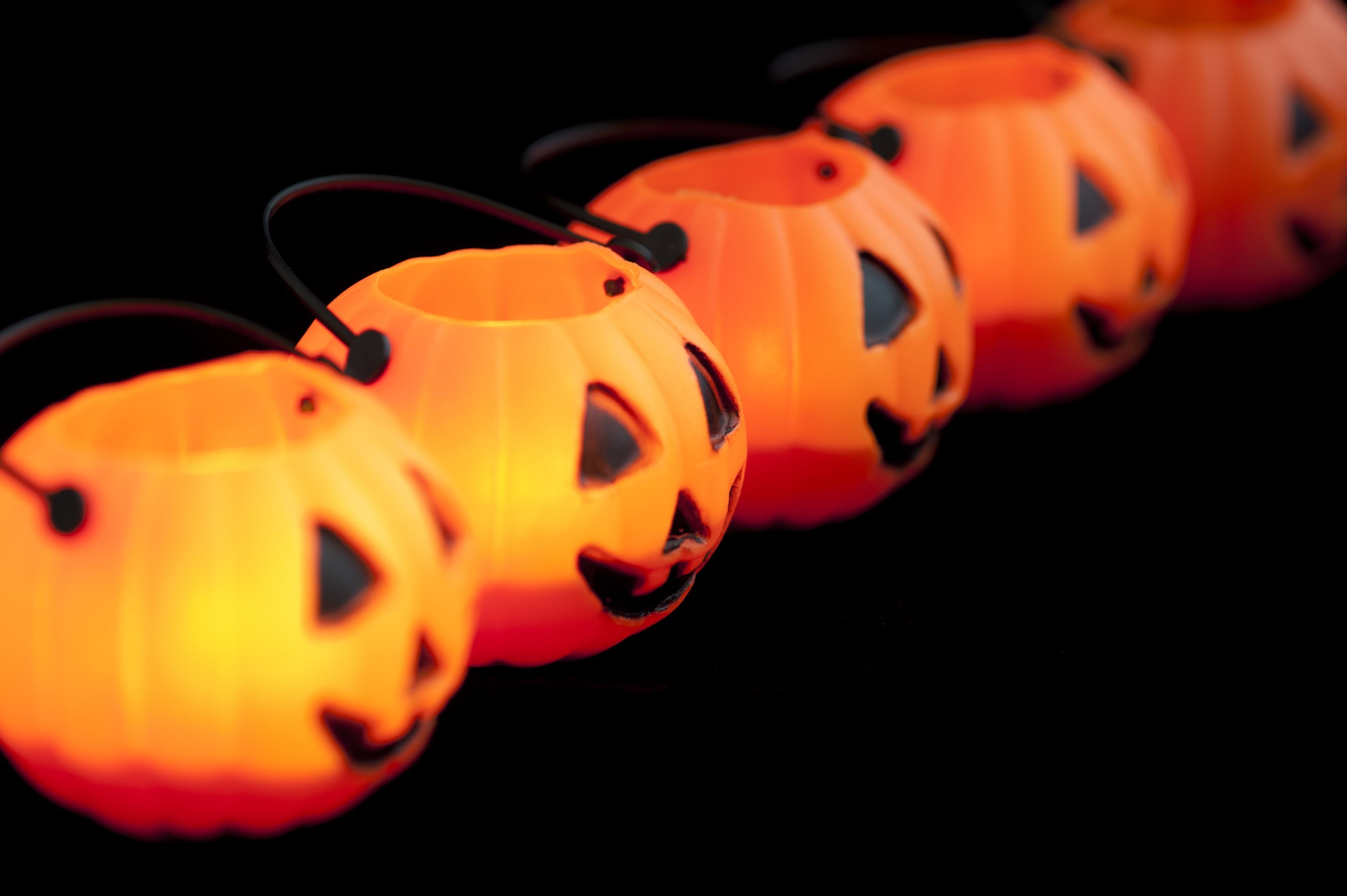 Receding diagonal line of ceramic pumpkin jack-o-lantern ornaments with cut out faces and handles on a black background with shallow dof and copyspace