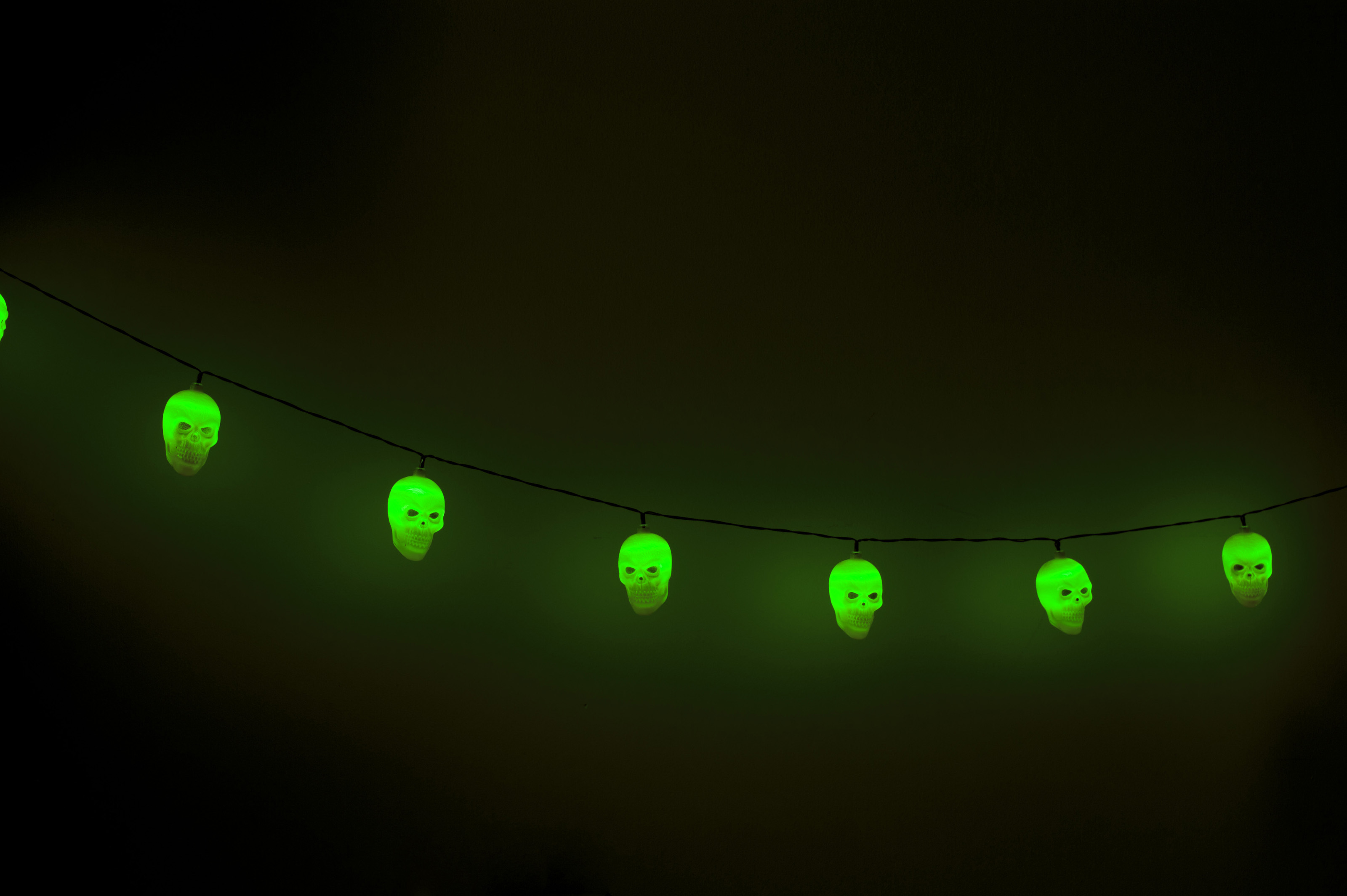 Six scull shaped lanterns hang in a row on cord glowing green against a dark background