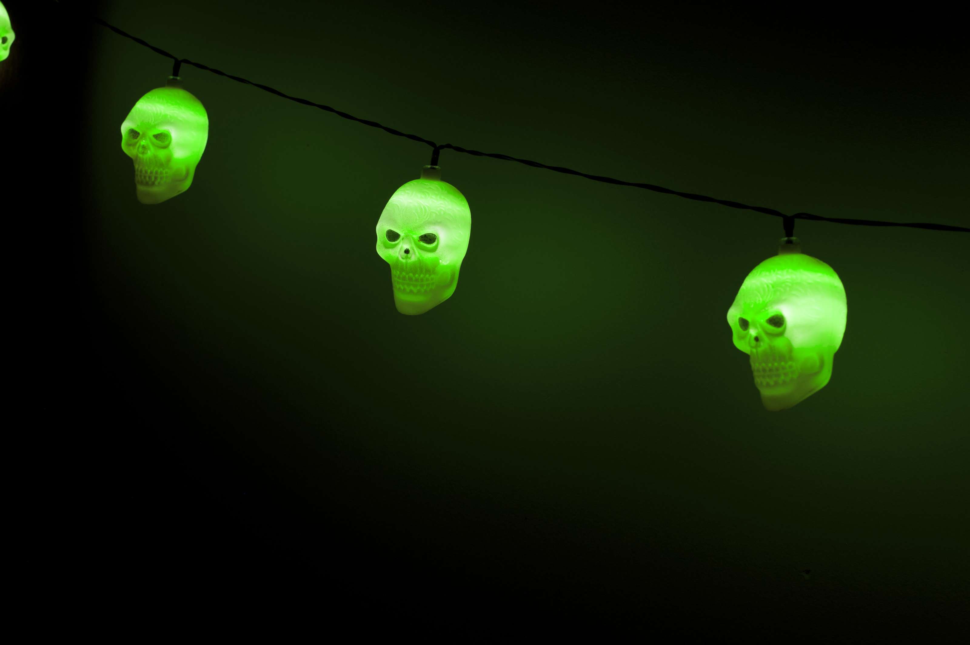 Image of Glowing string of ghoulish green skull lights Freebie.Photography