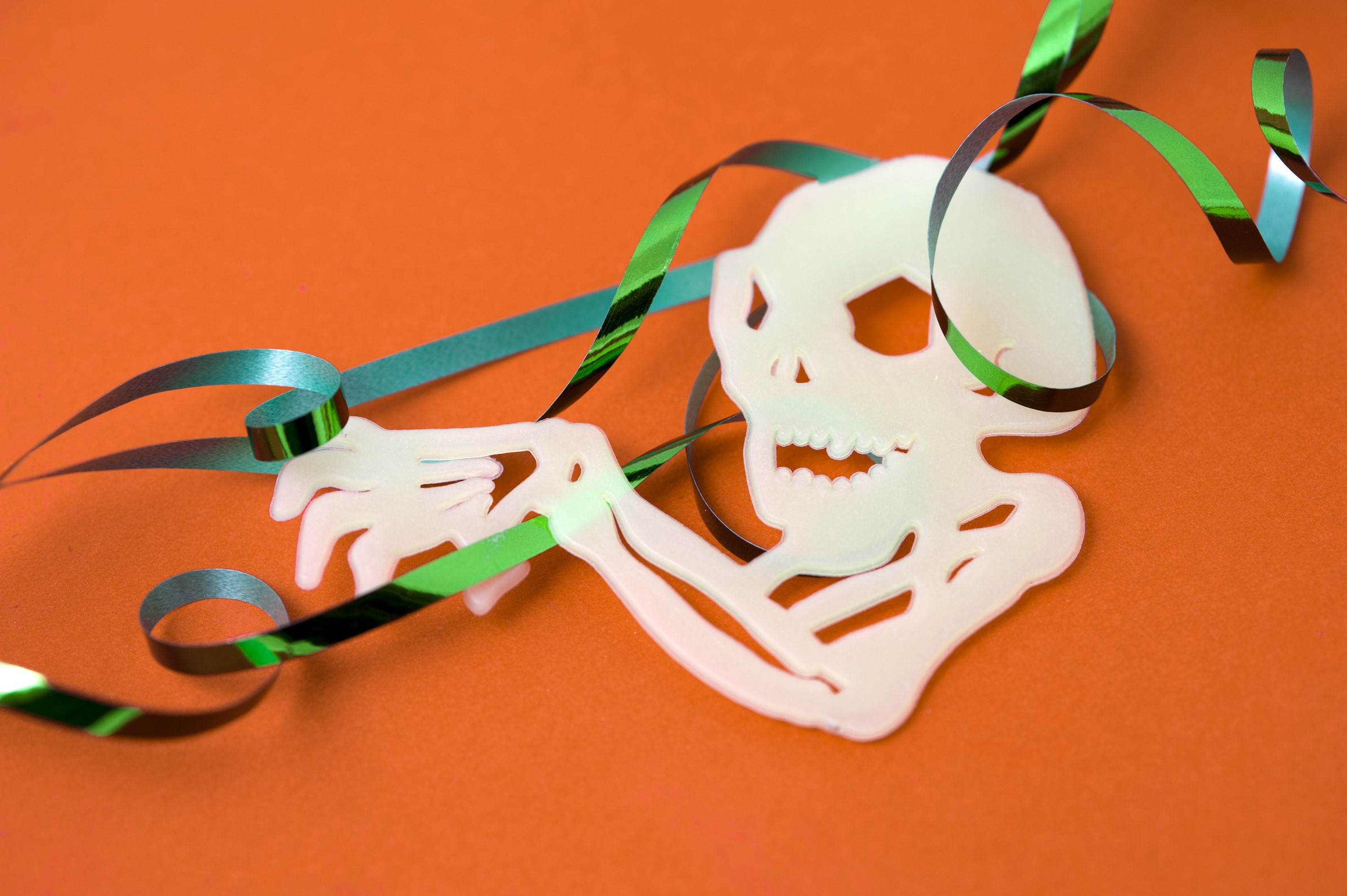 Spooking skeleton Halloween decoration with a skull and groping arm bones attached to a colourful party streamer to celebrate the holiday festival