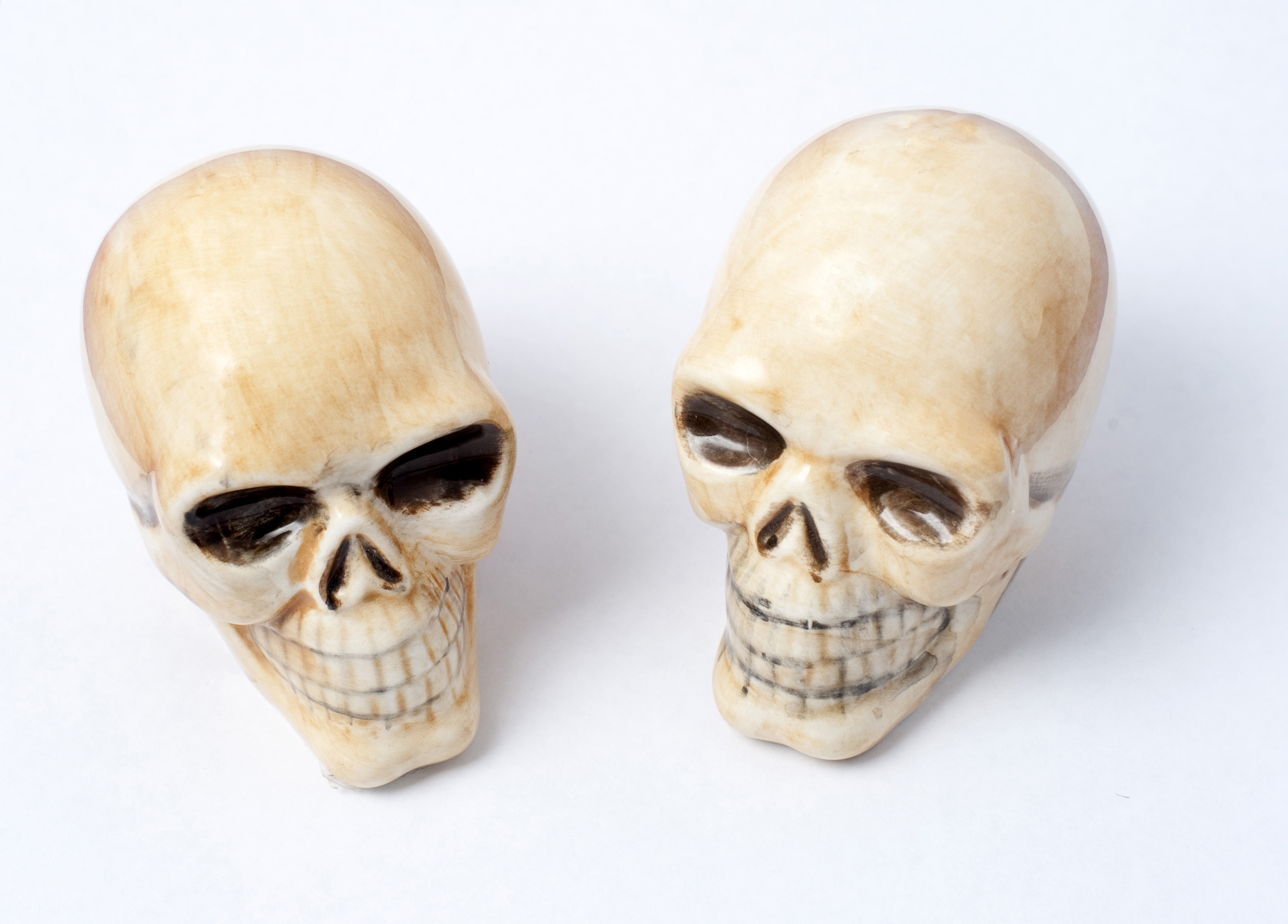 a pair of matching ceramic skull halloween ornaments