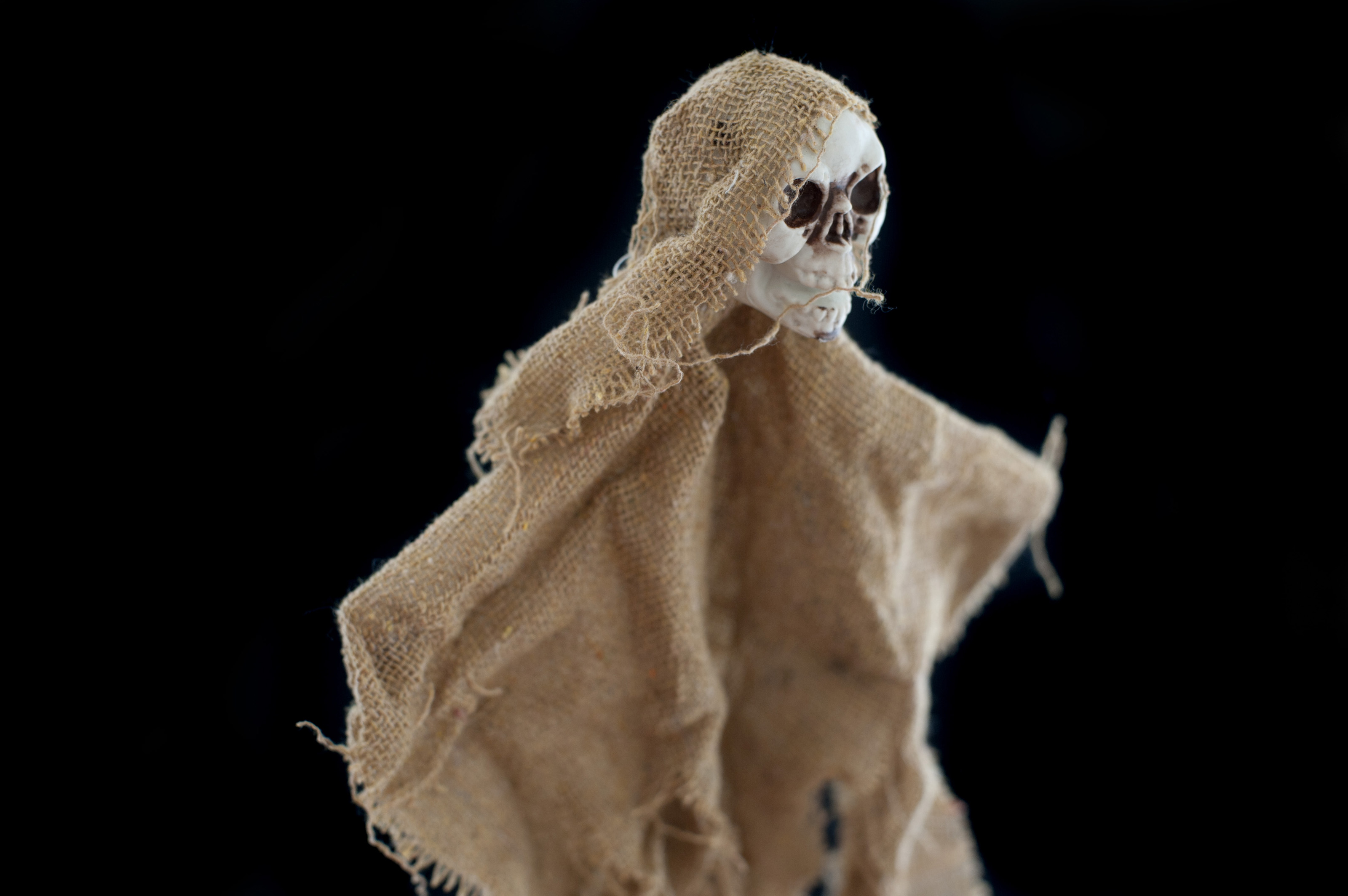 Spooky little doll made of burlap and skull over black background for concept about Halloween