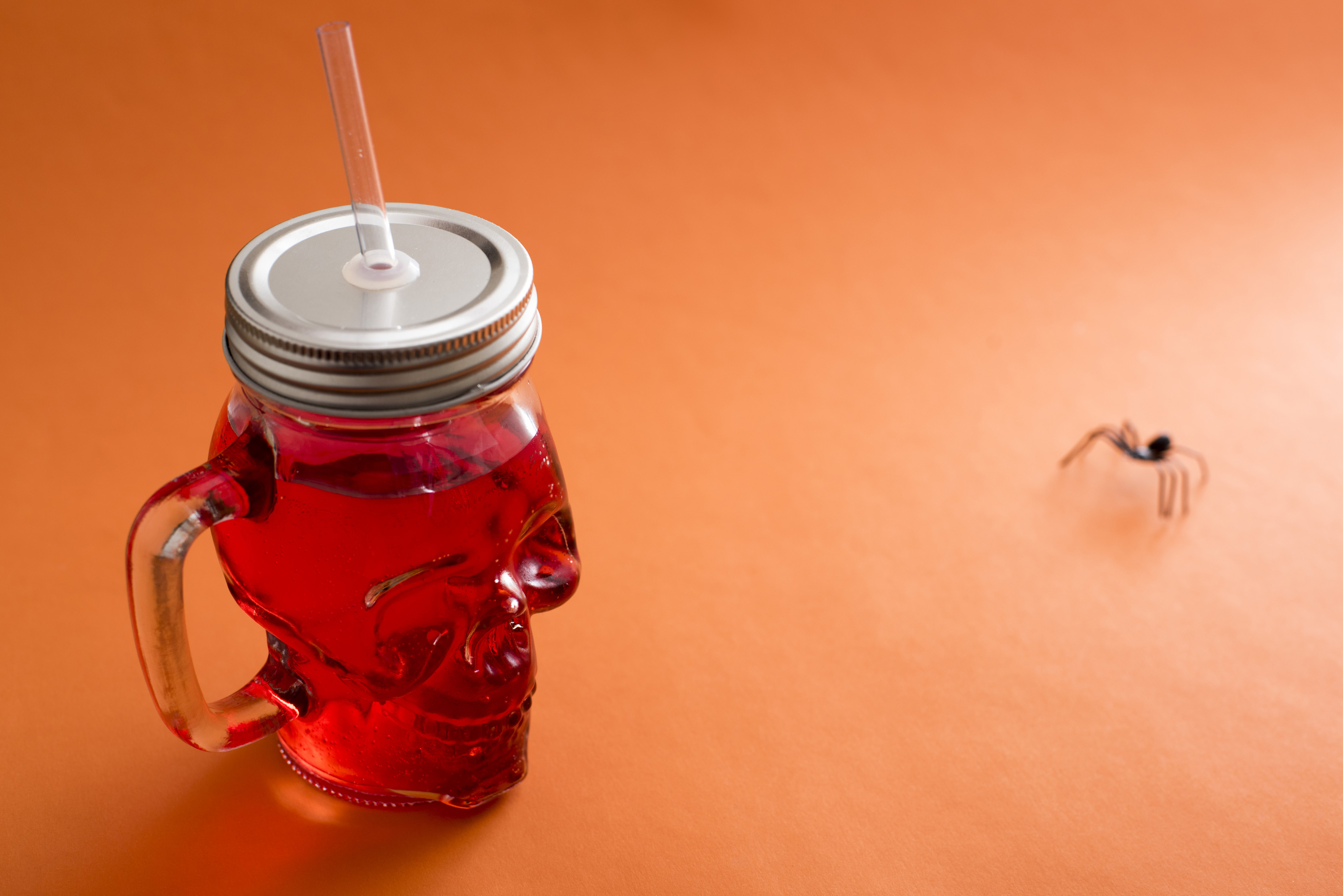 Novelty mason jar cup shaped like skull filled with red colored juice on orang table beside spider