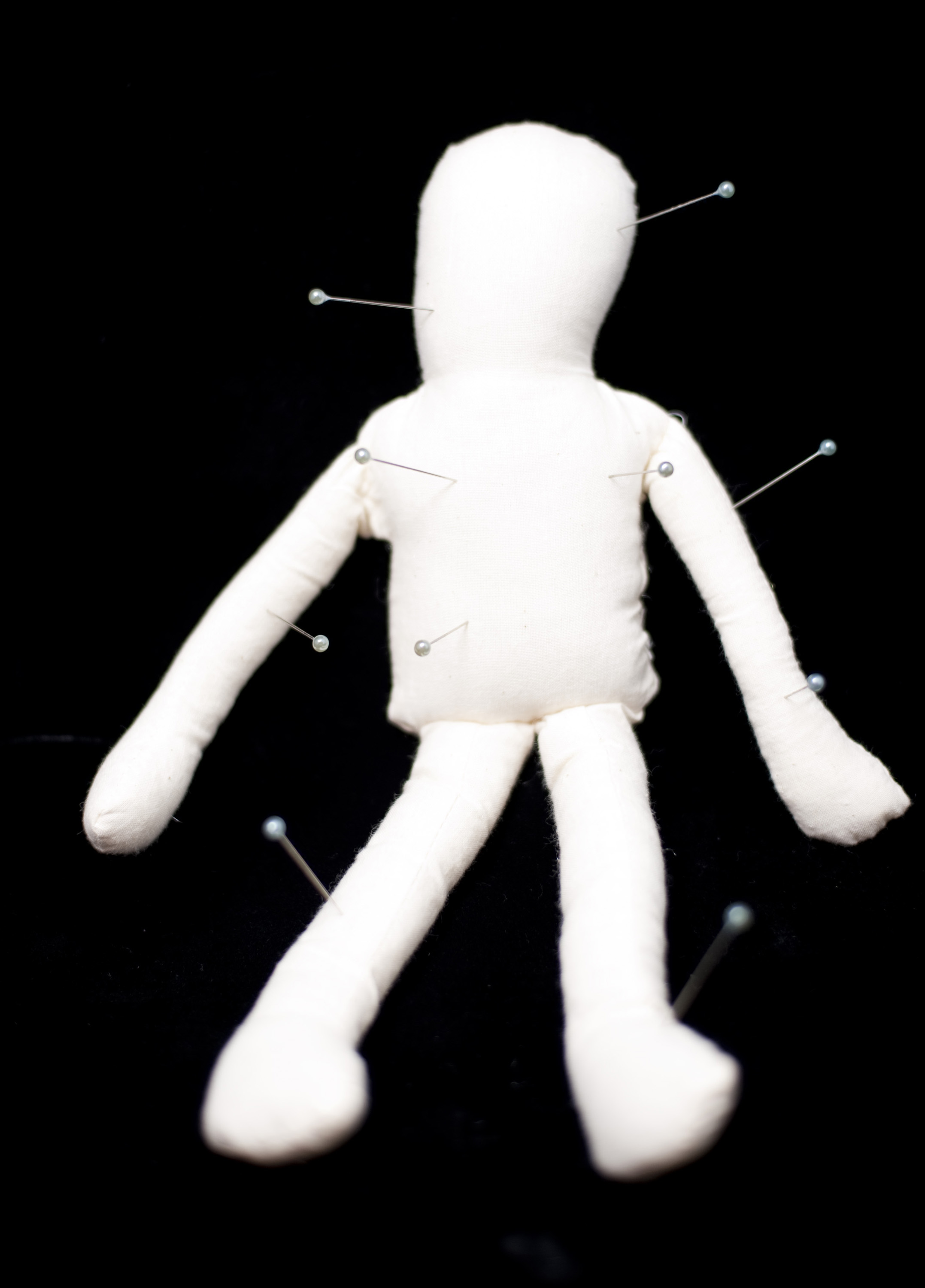 bad magic - a white voodoo doll with pins