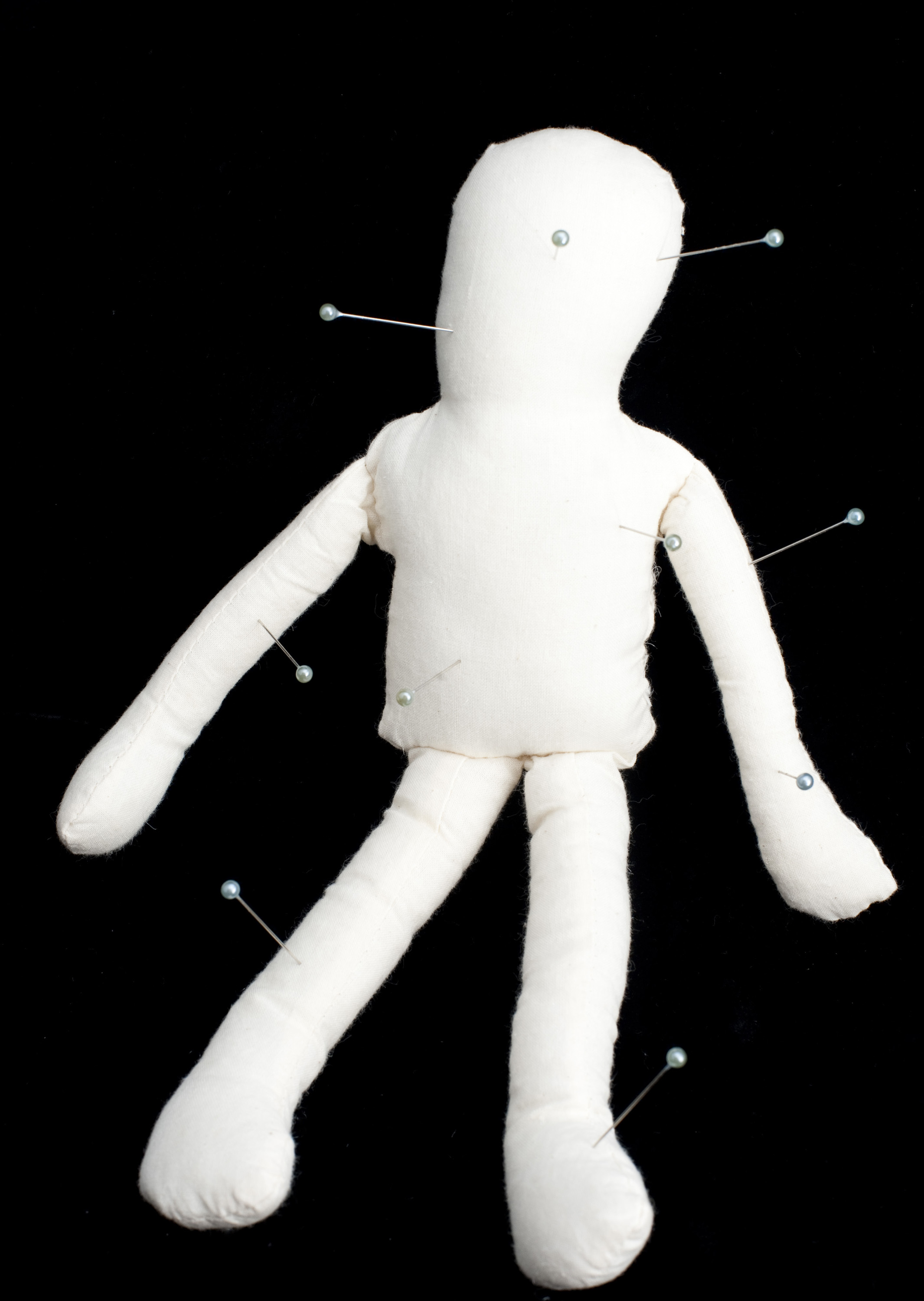 bad magic - a white voodoo doll with pins stuck all over it