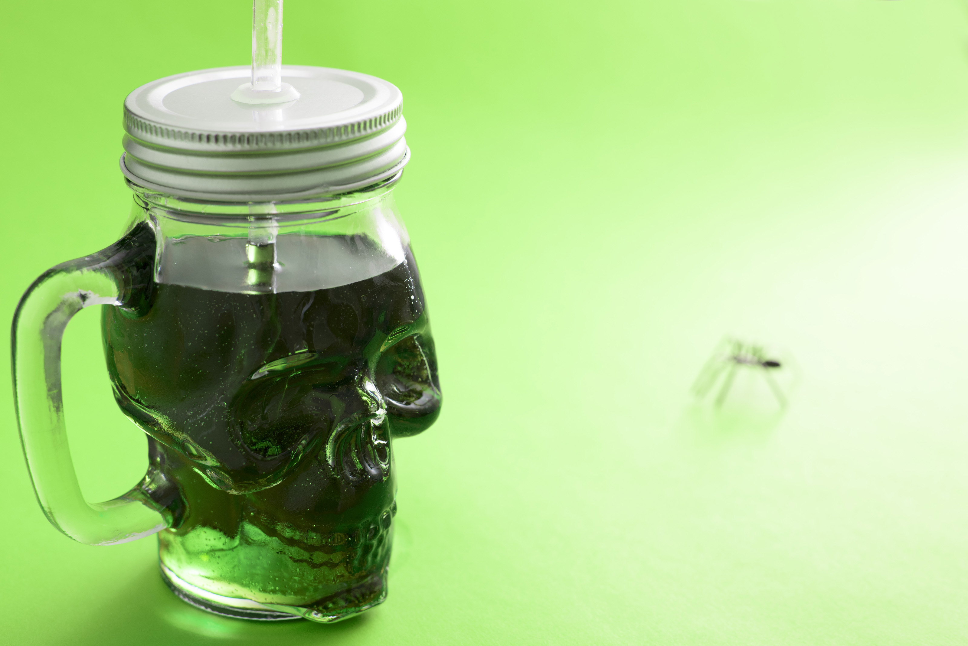 Green Halloween drink in a skull shaped glass mason jar with lid and straw over a graduated background with copy space