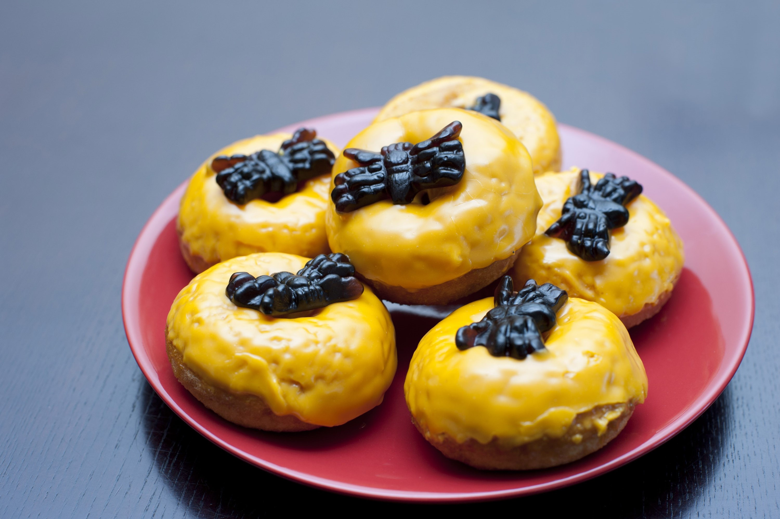 Plate of Halloween doughnuts with colourful orange icing and black jelly spiders for a creepy trick and treat
